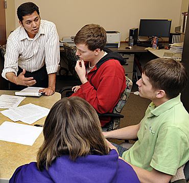 Abhijit Rao (standing), director of the College of Business Communication Center, and Tim Killian, one of the center's consultants, work with some students during a consulting session.