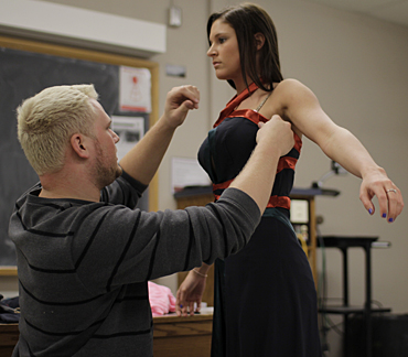 Student designer Zachary Davis works with student model Hannah Adams on the fitting for his fashion show entry. Photo by Allison Butler, The Fashion Show 2012